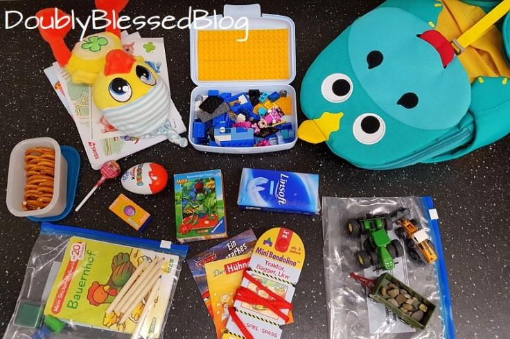 Inhalt des Kinderrucksacks zur Beschäftigung während dem Flug für einen Jungen. Minipuzzle, Plüschente, Lego Classic Box mit Legotape, Bandolino, Bagger, Traktor und Anhänger mit Kieselsteinen, Stempel, Malbüchlein, Farbstifte, Sticker, Pixibücher, Smarties, Überraschungsei, Lollipop, Brezel